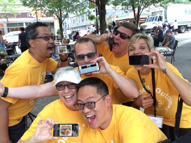 Shows a corporate team enjoying a smartphone scavenger hunt.